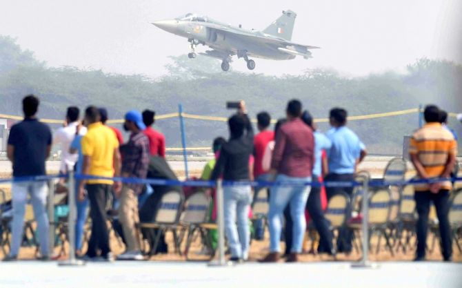 Visitors watch as IAF's Light Combat Aircraft Tejas lands after a fly pst during the 88th Air Force Day parade.